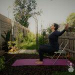Yoga am Sessel im Garten. Herzöffnende Yogahaltung im Sitzen.