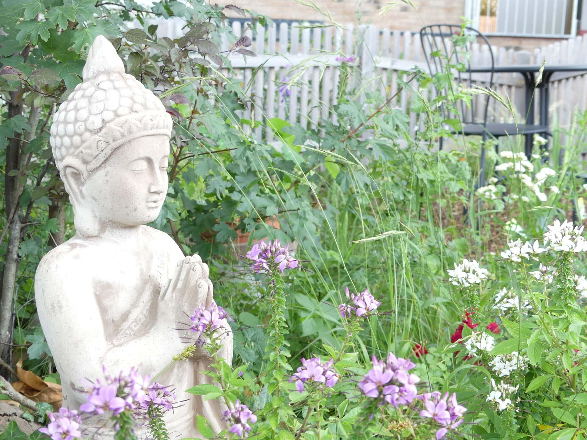 Statue eines meditierenden Buddhas mit den Händen in der Gebetshaltung in einem Garten.