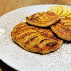 Drei Apfelpancakes serviert auf einem weißen Teller, garniert mit frischen Apfelscheiben und bestreut mit Zimt.