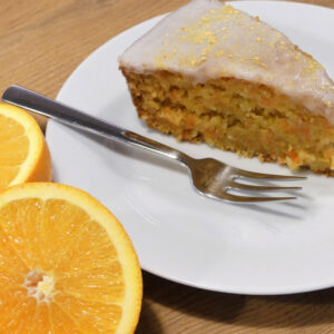 Ein Stück Karottenkuchen serviert auf weißen Teller mit einer Dessertgabel und dekoriert mit frischen halbierten Orangen.