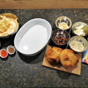 Alle vorbereiteten Zutaten für den Scheiterhaufen. Eine weiße Keramikauflaufform, eine Edelstahlschüssel mit geschälten Apfelscheiben, kleine Edelstahlschüsseln mit Rohrzucker, Vanillezucker, Margarine, Rosinen und Mandelblättchen, kleine weiße Schälchen mit Rum und Zimt, ein kleines Holzbrett mit zwei Osterpinzen darauf, ein Messbecher mit Pflanzenmilch und eine Packung Vanillepuddingpulver.