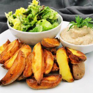 Goldbraune Erdäpfelspalten angerichtet auf einem weißen Teller, dazu weiße Bohnencreme in einer kleinen weißen Schale dekoriert mit Petersilie und eine weitere Schale mit grünem gemischten Salat.
